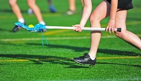 Girls lacrosse ball pick. High school girls varsity lacrosse player scoops up the ball from a turf field on a sunny day royalty free stock images