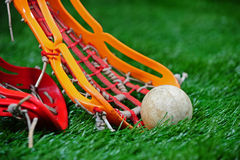 Girls Lacrosse stick scooping up the ball. A orange girls lacrosse head scooping up the ball on a turf field as a player with an red head tries to block and stop Royalty Free Stock Photo
