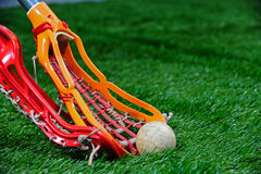 Girls Lacrosse sticks fight for the ball. Side view of a orange girls lacrosse head scooping up the ball on a turf field as a player with an red head tries to royalty free stock photography