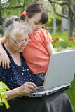 Girls with laptop. Girl with grandma in garden Stock Photography