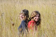 Girls laugh in an autumn field Royalty Free Stock Photo