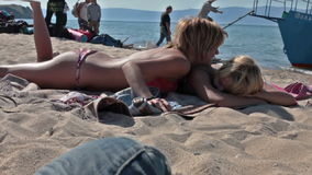 Girls laughing on beach blanket. Two young women laying on blanket at beach laughing with boat in water in background stock footage