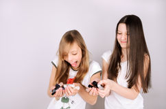 Girls laughing and holding in hands nail polish. On the light grey background, horizontal Stock Images