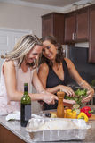 Girls laughing while making diner. Girls laughing in the kitchen while making dinner stock photo