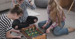 Girls laughing while playing foosball at home. Excited teenage girls laughing while playing foosball at home stock video footage