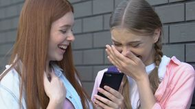 Girls laughing at shameful post with classmate in social media, cyberbullying. Stock footage stock video footage