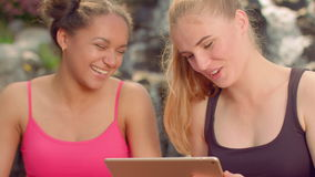 Girls laughing. Young women gossiping. Closeup of girlfriends read tablet. Outdoor. Multicultural women talking together. Joyful girls networking on tablet stock video footage