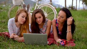 Girls lay on grass, use laptop together during picnic in the countryside. Three girls on vacation stock video footage