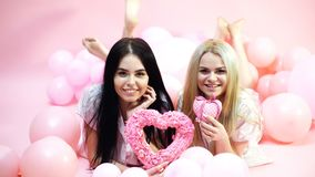 Girls lay near balloons, holds heart toys, pink background. Valentines day concept. Blonde and brunette on smiling faces