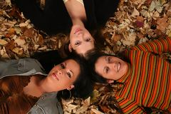 Girls laying in the autumn leaves. Royalty Free Stock Photo