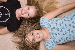 Girls laying on floor. Two teenage girls laying with heads together on the floor Royalty Free Stock Image