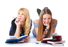 Girls laying on the floor and reading book Royalty Free Stock Image