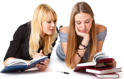 Girls laying on the floor and reading book Stock Photo
