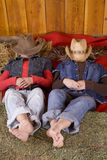 Girls laying with hats over heads feet on hay Stock Photography