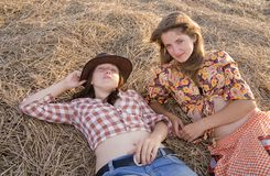 Girls laying in hay. Country girls on fresh hay in summer Stock Images