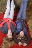 Girls laying on red blanket one tongue Stock Images