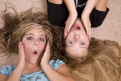 Girls laying on with surprised look. Two teenage girls with a surprised look on their faces Stock Photography