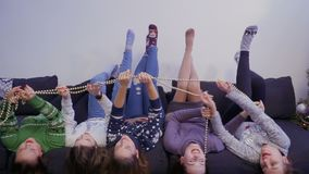 Five girls lying upside down on sofa and have fun stock video