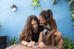 Girls leaning over a table, one of them writes. Two girls sitting on a single chair, one of them writes on a paper Royalty Free Stock Photos