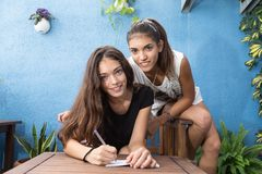 Girls leaning over a table, one of them writes. Two girls sitting on a single chair, one of them writes on a paper Royalty Free Stock Photography