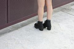 Girls leg. Girl wearing black shoe standing on a concrete floor royalty free stock photos