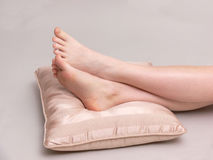 Girls legs. A girl is resting her legs on a cushion on white background Royalty Free Stock Image