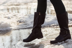 Girls legs in boots trying to go on spring puddle Stock Images