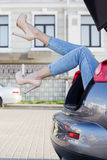 Girls legs in car trunk is wearing fashion heels Stock Photo