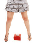 Girls legs with gift. A closeup of a young girls spread legs with high heels and a red present Stock Photos
