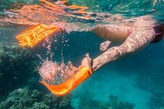 Girls legs in orange flippers underwater in sea near coral reef. Girls legs in orange flippers underwater in Red sea near coral reef Stock Photo