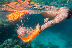 Girls legs in orange flippers underwater in sea near coral reef Stock Photo