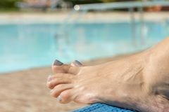 Girls legs by pool. Relaxing at the pool. womans feet against swimming pool on resting.  stock photography