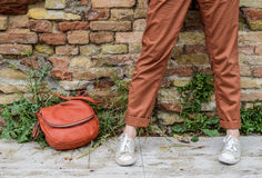 Girls legs stand near a brick wall, hipster style. Royalty Free Stock Images