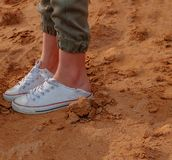 Girls legs in trainers on bare dirt. Shot with copyspace royalty free stock image