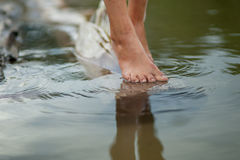 Girls legs on the water. Girl's legs on water standing on a log Royalty Free Stock Image