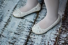 Girls legs with white socks in white slippers. Outdoor over wooden floor Royalty Free Stock Image