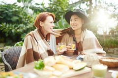 Girls with lemonade. Two intercultural girlfriends wrapped in plaid sitting by table and having drinks Royalty Free Stock Images