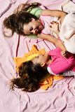 Girls lie on white and pink bed sheets background tickling. Pajama party and childhood concept. Schoolgirls in pink pajamas wallow on colorful pillows, top royalty free stock images