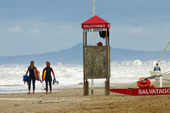 Girls and lifeguard. Girls who have been surfing on a windy day at Rimini in Italy Royalty Free Stock Photography