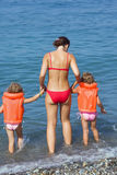Girls in lifejackets with woman coming into sea Stock Photography