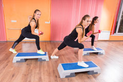 Girls Lifting Weights While Stepping on Platforms Stock Photography