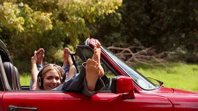 Girls listening to music in a red car stock footage