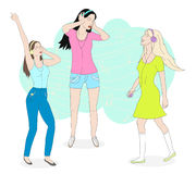 Girls listening to music. Three beautiful girls listening music in headphones and dancing Stock Photo
