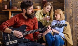 Girls listening to song performed by handsome bearded musician. Guitarist entertaining guests at party. Man with hipster. Beard playing electrical guitar royalty free stock images
