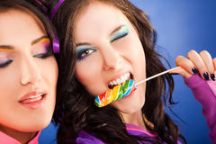 Girls lollipop blink. Close-up of two beautiful girls - one of them giving a blink and biting lollipop stock photos