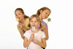 Girls with lollipop on a white background Stock Photos