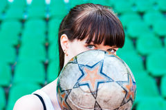 Girls look for the ball. Girl holding a ball and watching over him Royalty Free Stock Image