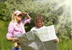 Girls look at the map Royalty Free Stock Photo