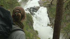 Girls look at waterfall in mountains stock video footage