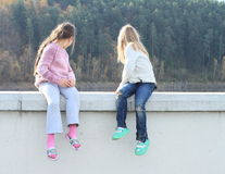 Girls looking behind wall Royalty Free Stock Photo